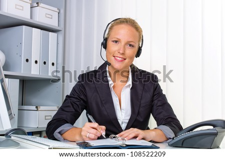 a friendly young woman with a headset on the phone with customer service to a customer. hotline staff friendly. - stock photo