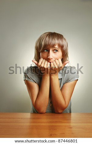 A frightened young girl sitting at the desk, isolated on grey - stock photo