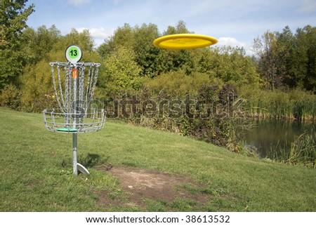 A frisbee golf target with a disc inbound - stock photo