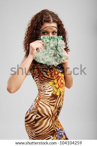 A frisky woman is standing and holding a reticule in front of her face. The merry girl is looking out from her purse. She is wearing a summer variegated dress. - stock photo