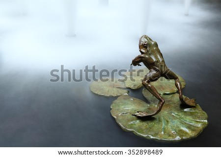 A frog jumps into water - stock photo