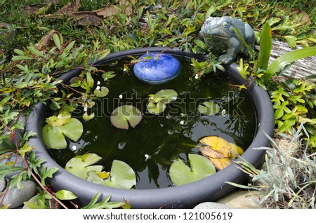 A frog statue decor and a water pond in the garden. - stock photo