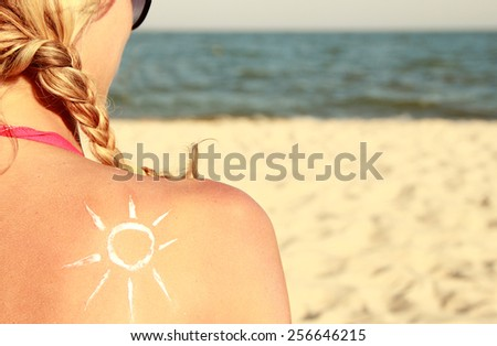a from the sun cream on the female back on the seaside - stock photo