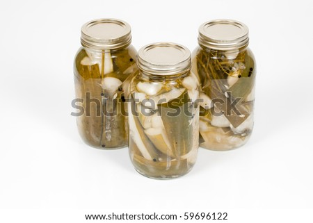 A front angled  studio view of three jars of homemade pickles. - stock photo
