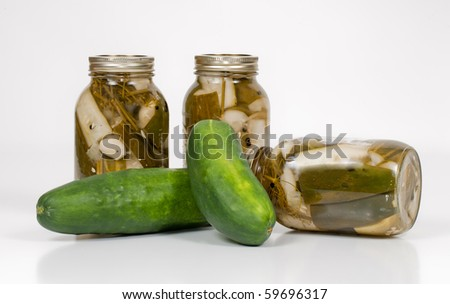 A front close-uo studio shot of three cans of homemade pickles in a canning jar with two cucumbers. - stock photo
