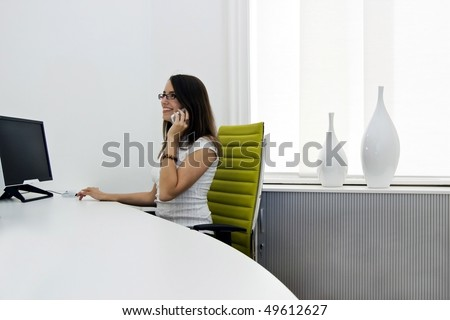 a front desk lady doing her job very well and cheerfully. - stock photo