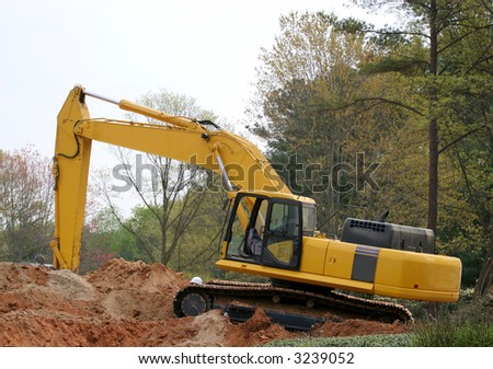 A front end loader atop a pile of dirt - stock photo