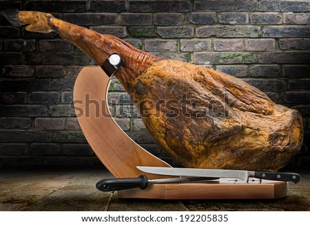 A front leg of Serrano ham mapped on a wooden stand on artistic background. - stock photo