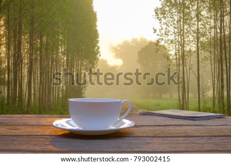 A front selective focus picture of a farmer's coffee cup in the morning sunrise beside foggy field