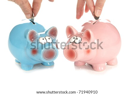A front studio isolation shot on a white background of two coins being dropped into a pink and blue ceramic piggy banks as a metaphor for a joined savings account.