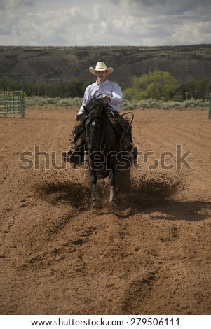 a front view of a cowboy on his horse kicking up dirt. - stock photo