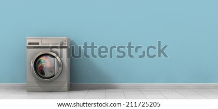 A front view of a regular brushed metal washing machine filled with clothing in an empty room with a shiny tiled floor and a baby blue wall - stock photo