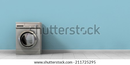 A front view of an empty regular brushed metal washing machine in an empty room with a shiny tiled floor and a baby blue wall - stock photo