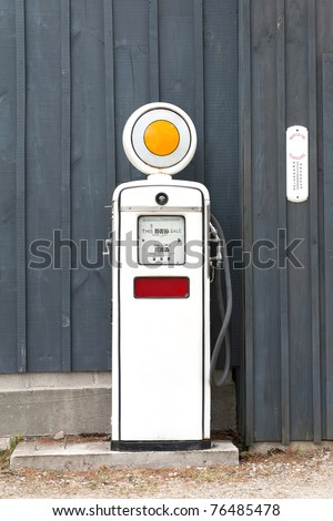 A front view of an old fashioned gasoline pump from the 1960's with 42 1/2 cents per gallon on the meter against a blue board and batten background. - stock photo