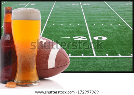 A frothy glass of beer with an American Football in front of a big screen television. Great for Super Bowl themed projects. - stock photo