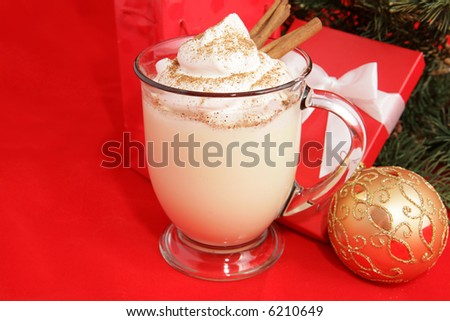 A frothy mug of eggnog under the Christmas tree.  Red background with room for text.