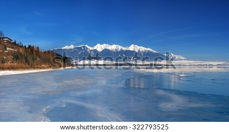 A frozen Liptovska Mara lake with the Rohace mountains and the peak of Krivan. The Rohace mountains are part of the Western Tatras, whereas the Krivan peak belongs to the High Tatras mountain range.