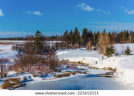 A frozen stream in rural Prince Edward Island, Canada. - stock photo