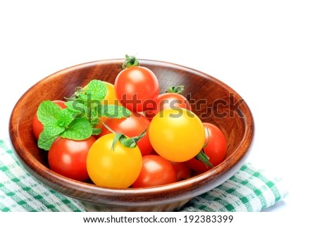 A fruit bowl filled with orange and red tomatoes. - stock photo