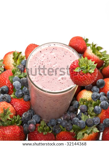 A fruit smoothie drink made of banana, blueberries, strawberries, etc. surrounded by fresh fruit - stock photo