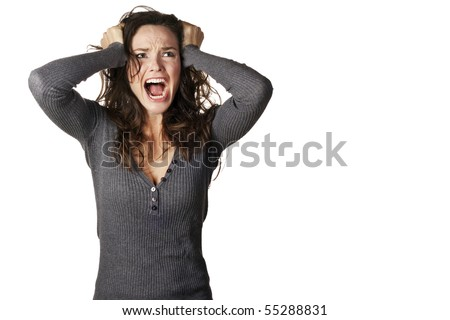 A frustrated and angry woman is screaming out loud and pulling her hair.