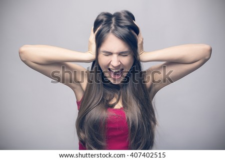 A frustrated and angry woman is screaming out loud and squeezes her head - stock photo