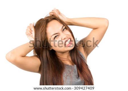 A frustrated Asian girl in gray, clenching her teeth, pulling her light brown hair during temper tantrum outburst, fed up, annoyed, irritated. Thai national of Chinese origin. Horizontal