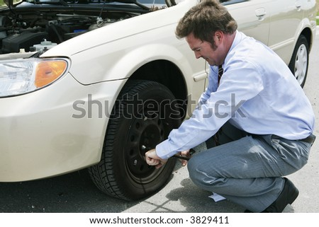 A frustrated businessman loosening lug nuts on his car's flat tire. - stock photo