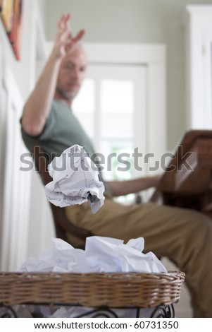 A frustrated man in his home office, throwing away a crumpled piece of paper.