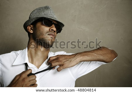 A frustrated model acts sexy as he undresses in studio - stock photo