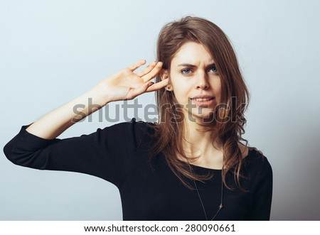 A frustrated pretty woman putting her finger in her ear - stock photo
