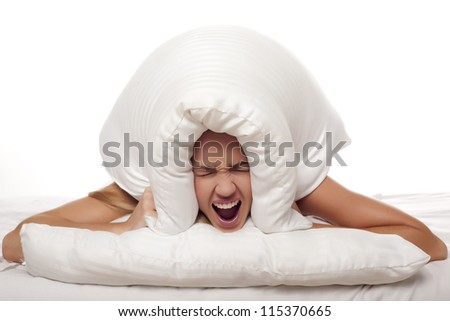A frustrated woman is screaming as she is holding a pillow over her head. Screaming woman. - stock photo