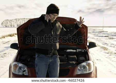 A frustrated young man is calling for help on his cell phone because his car broke down. - stock photo