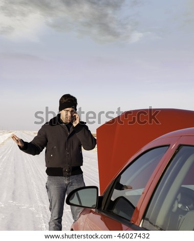 A frustrated young man is calling for help on his cell phone because his car broke down in the winter.