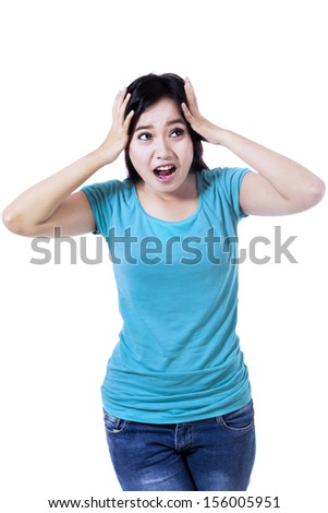 A frustrated young woman is screaming out loud, isolated on white background - stock photo