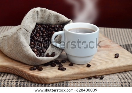 A full bag of brown coffee beans and a white cup of hot coffee lies on a wooden surface. Attributes related to the preparation of natural coffee