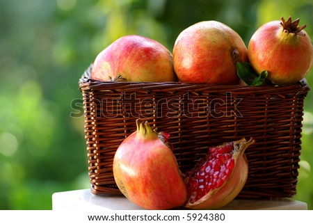 A full basket with red fruits of the Autumn:Pomegranates - stock photo