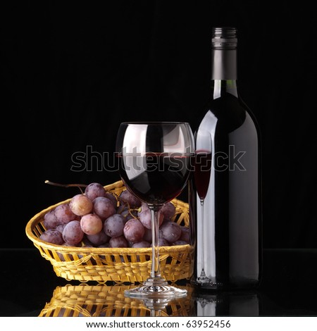 A full bottle of red wine, a glass of wine and black grapes in a wicker basket on a black background - stock photo