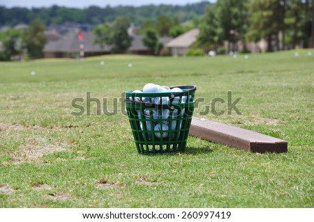 A full bucket of golfballs on the driving range  - stock photo