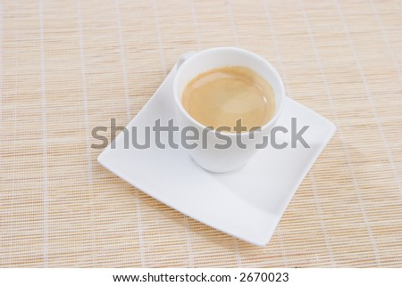 A full cup of espresso on a white square saucer