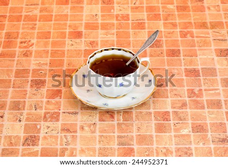 A full cup of tea, spoon and saucer are on multicolor table - stock photo