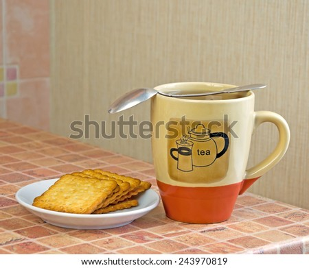 A full cup of the tea, white saucer with biscuits and silver teaspoon are on multicolor table - stock photo