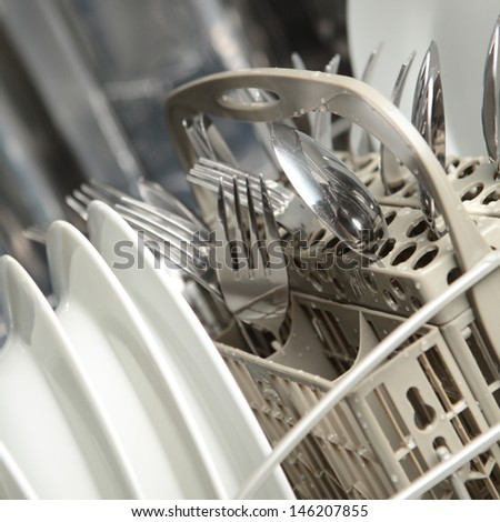 A full dishwasher with clean dishes. - stock photo