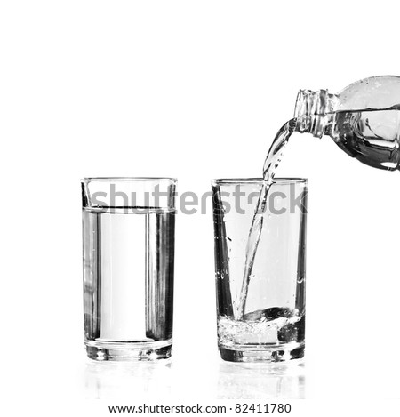 a full glass of water and an empty glass to be filled - stock photo