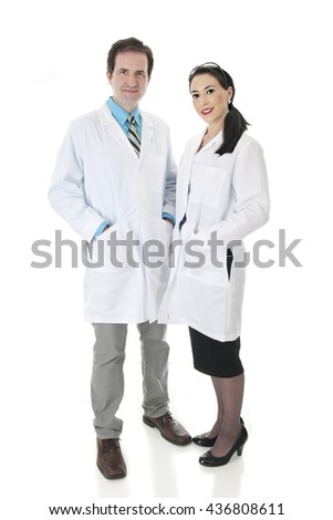 A full length image of a male and female medical workers.  They are happily standing together in their lab coats.  On a white background. - stock photo