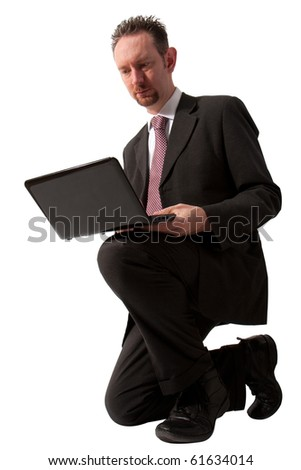A full length of a mid thirties business man.  The man is kneeling down and using a black laptop computer.  Studio isolated on a white background. - stock photo