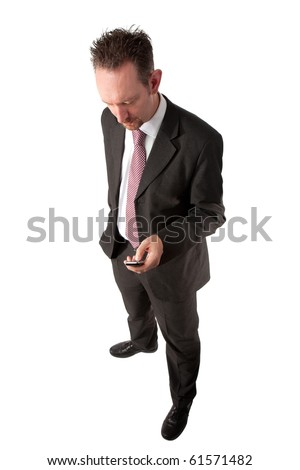 A full length of a mid thirties business man.  The man is wearing a dark grey suit and tie.  The man is looking down towards a mobile phone that he is texting on. - stock photo