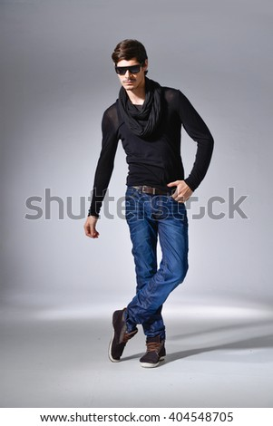 A full-length portrait of a young man in sunglasses isolated on light background - stock photo