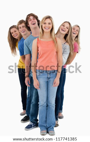 A full length shot of a group of people looking at the camera at various angles - stock photo