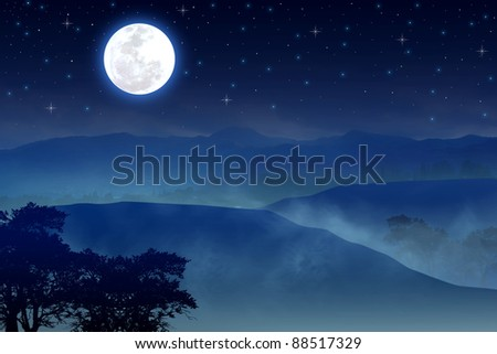A full moon over misty hills - stock photo
